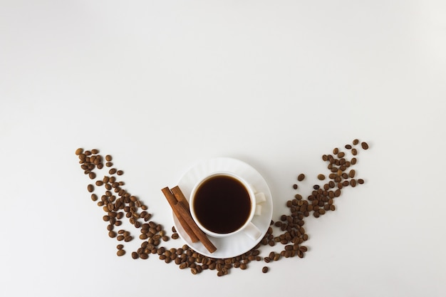Weiße schale mit kaffee, kaffeebohnen auf einer weißen oberfläche. flachgelegt, draufsicht