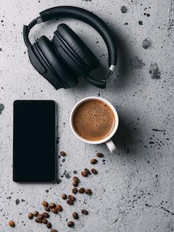 Weiße schale mit wohlriechendem espresso zum frühstück. telefon und kopfhörer auf dem tisch. wochenende