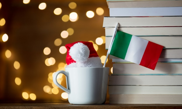 Weiße schale und weihnachtshut mit italien-flagge nahe büchern