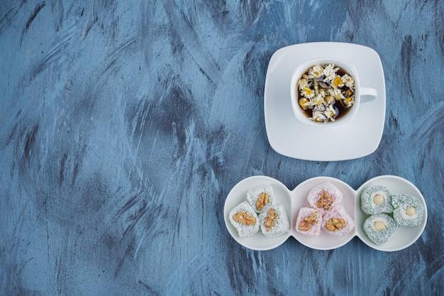 Weiße schalen mit verschiedenen süßen köstlichkeiten mit nüssen und tee auf blauer oberfläche.