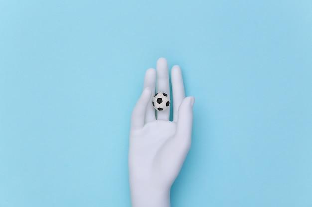 Weiße schaufensterpuppe hand hält mini-fußball auf blauem hintergrund.