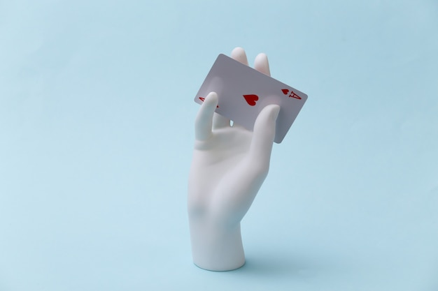 Weiße schaufensterpuppe hand mit herz-ass steht auf blauem hintergrund. poker, kartenspiel