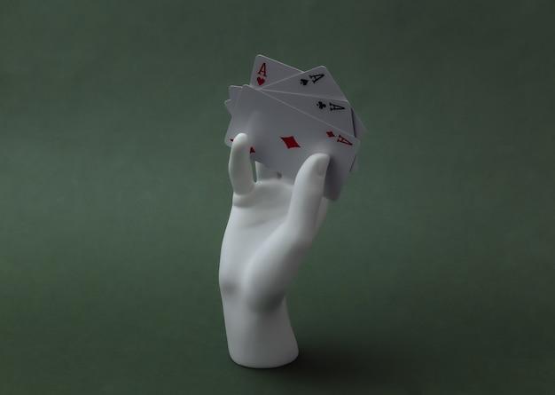 Weiße schaufensterpuppe hand mit vier assen steht auf grünem hintergrund. poker, kartenspiel