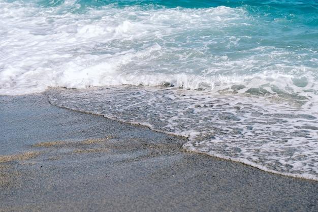 Weiße schaumige wellen auf sandstrandnahaufnahme. am sonnigen sommertag am meer. sommerferienzeitkonzept.