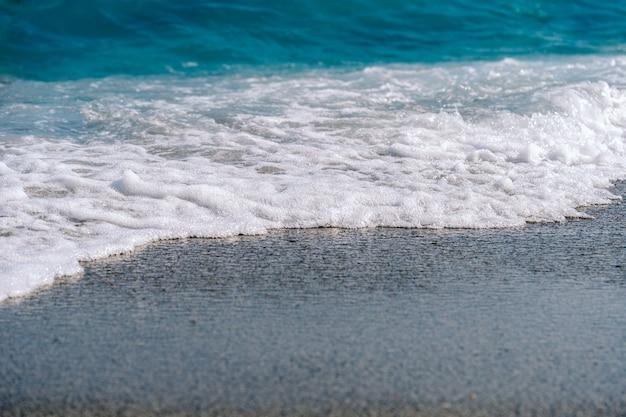 Weiße schaumige wellen auf sandstrandnahaufnahme. am sonnigen sommertag am meer.