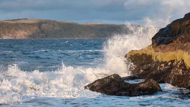 Weiße schaumwellen laufen am felsigen ufer des weißen meeres nordische barentssee-ozean
