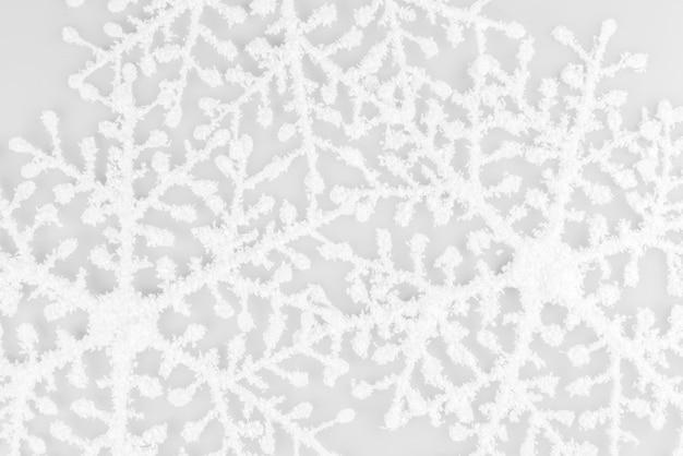 Weiße schneeflocken lokalisiert auf weißem hintergrund. weihnachtskomposition. rahmen aus weißen schneeflocken auf weißem hintergrund.