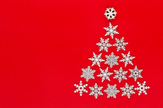 Weiße schneeflockendekoration auf rotem hintergrund. flache lage, draufsicht