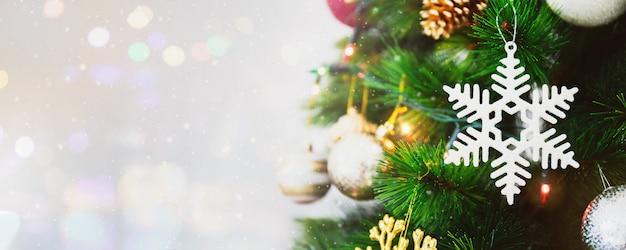 Weiße schneeflockendekorationsverzierung auf weihnachtsbaumhintergrund mit schneefällen, unschärfe bokeh und kopienraum.