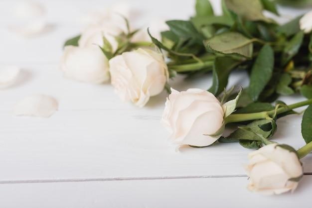 Weiße schöne rosen auf hölzernem schreibtisch