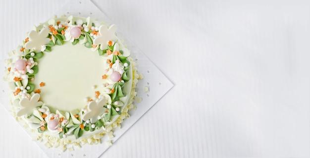 Weiße schokolade geburtstagstorte. ist cremig, weiß und grün, mit schönen spiralförmigen blütenblättern. auf einem weißen gewebehintergrund