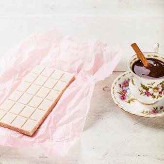 Weiße schokolade in papier mit heißer schokolade in der tasse eingewickelt