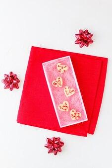 Weiße schokoladenherzen mit erdbeeren in einer geschenkbox auf einer roten serviette
