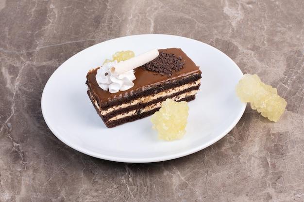 Weiße schokoladenkuchen auf holzbrett mit stoff.