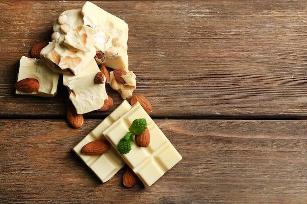 Weiße schokoladenstücke mit nüssen auf farbigem holzhintergrund