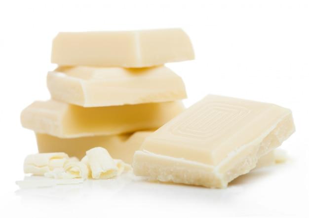 Weiße schokoladenstücke und -locken lokalisiert auf weiß.