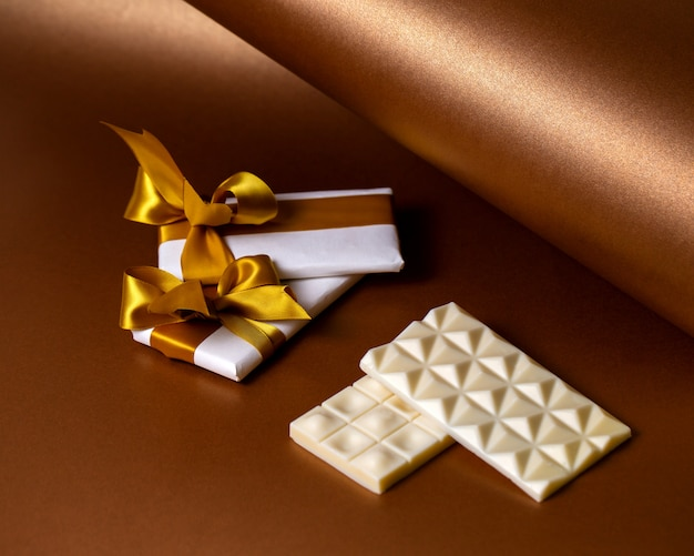 Weiße schokoriegel aus der seitenansicht mit schokolade, eingewickelt in weißes papier mit goldenen bändern