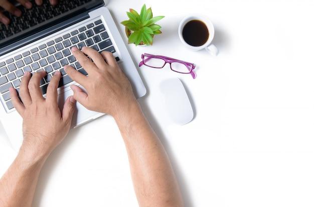 Weiße schreibtischtabelle mit dem handmann, der laptop tpying ist.