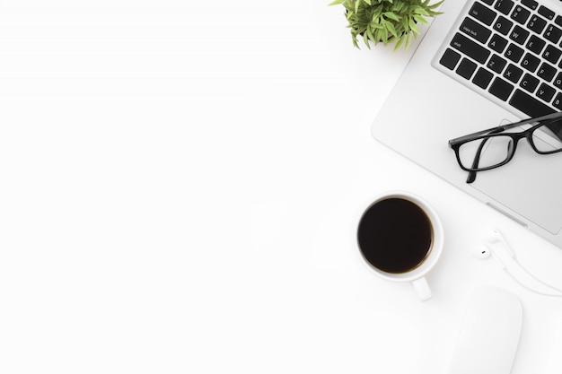 Weiße schreibtischtabelle mit laptop-computer, tasse kaffee und büroartikel.
