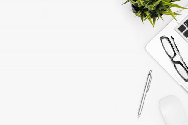 Weiße schreibtischtabelle mit laptop-computer und versorgungen.