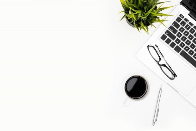 Weiße schreibtischtabelle mit laptop, tasse kaffee und versorgungen.