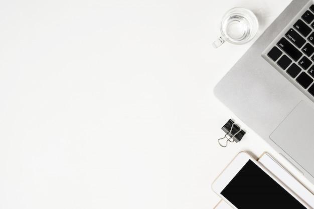 Weiße schreibtischtabelle mit laptop und versorgungen. draufsicht mit copyspace, flache lage.