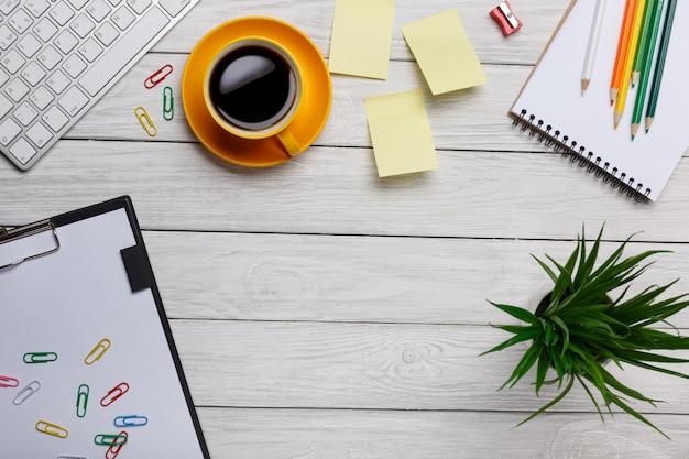 Weiße schreibtischtabelle mit leerem notizbuch, computer, versorgungen und kaffeetasse.