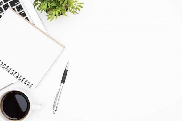 Weiße schreibtischtabelle mit leerem notizbuch, laptop-computer, tasse kaffee und versorgungen. draufsicht, flach zu legen.