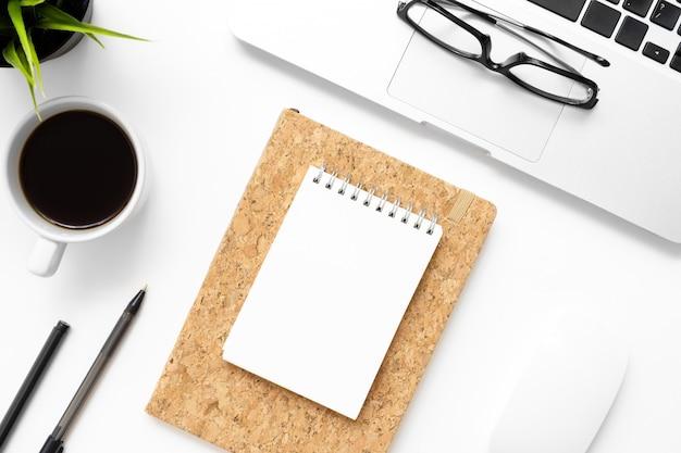 Weiße schreibtischtabelle mit leerem notizbuch, laptop, tasse kaffee und büroartikel.