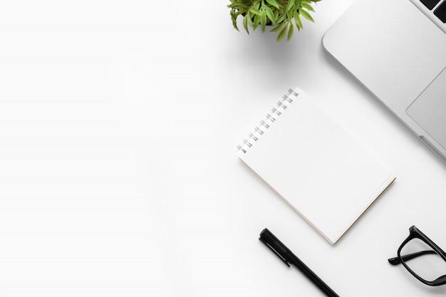 Weiße schreibtischtabelle mit leerem notizbuch, laptop und anderem büroartikel. draufsicht mit kopienraum, flache lage.