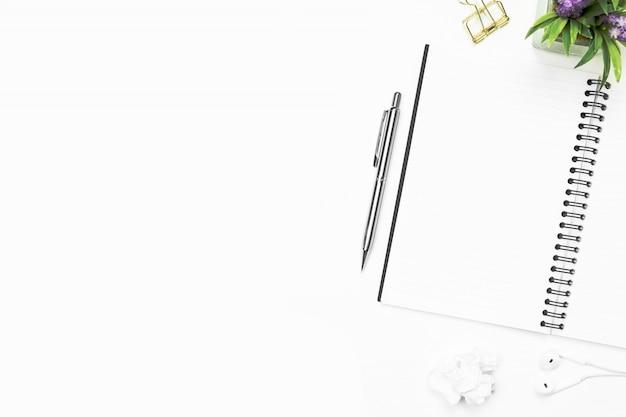 Weiße schreibtischtabelle mit leerem notizbuch und versorgungen. draufsicht mit kopienraum, flache lage.