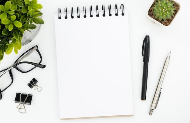 Weiße schreibtischtabelle mit leerer notizbuchseite und -versorgungen. draufsicht, flach zu legen.