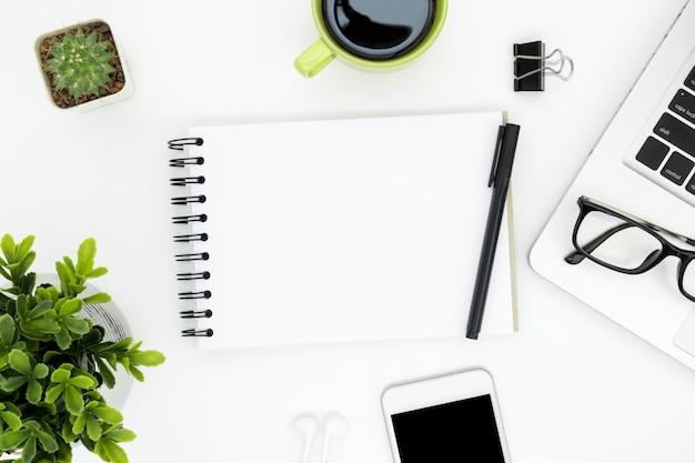 Weiße schreibtischtabelle mit leerer notizbuchseite und -versorgungen.