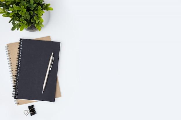 Weiße schreibtischtabelle mit notizbüchern, stift und anlage. draufsicht mit copyspace, flache lage.