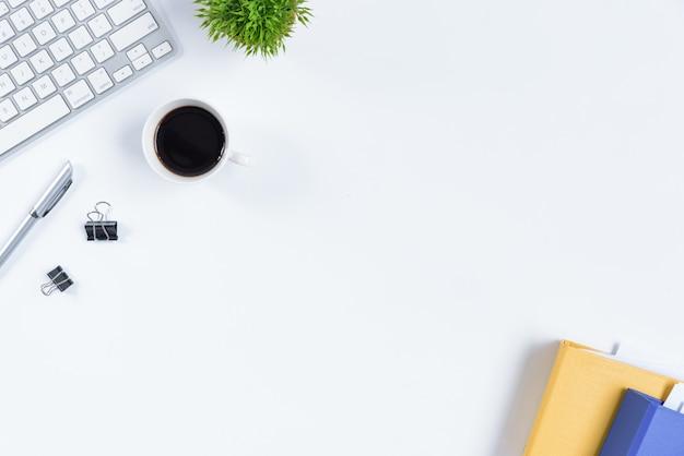 Weiße schreibtischtabelle und -ausrüstung für das arbeiten mit schwarzem kaffee in der draufsicht und im flachen strahlnkonzept.