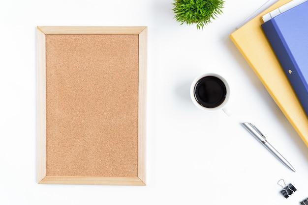 Weiße schreibtischtabelle und -ausrüstung für das arbeiten mit schwarzem kaffee und leerem brett in der draufsicht und im flachen strahlenkonzept.