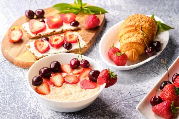 Weiße schüssel brei mit erdbeeren und kirschen, croissants und knäckebrot mit käse und erdbeeren