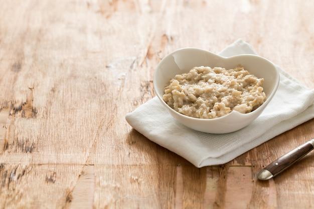 Weiße schüssel haferbrei. gesundes haferflockenfrühstück