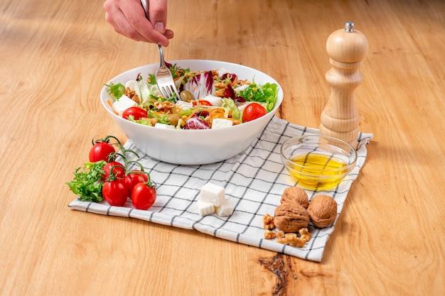 Weiße schüssel mit eisbergsalat und rucola von intensiver grüner und violetter farbe mit einer mischung aus sehr gesunden zutaten für eine diät wie nüssen, käse, kirschtomaten, oliven, karotten und mais.
