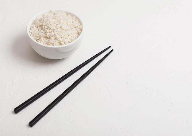Weiße schüssel mit gekochtem bio-basmati-jasminreis mit schwarzen stäbchen