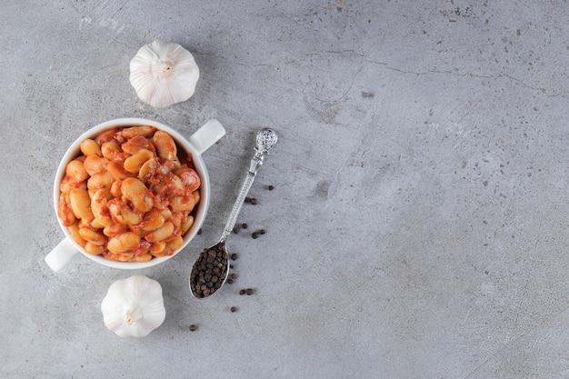 Weiße schüssel mit gekochten sojabohnen und knoblauch auf steinhintergrund.