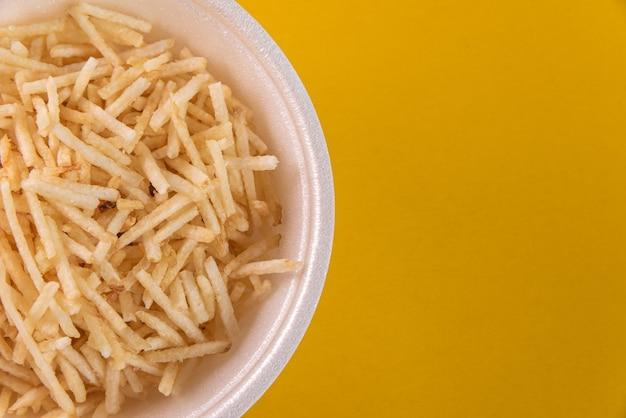 Weiße schüssel mit kartoffelstroh auf gelbem hintergrund