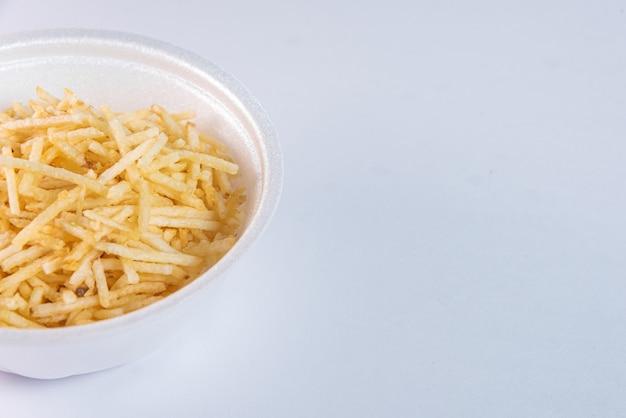 Weiße schüssel mit kartoffelstroh auf weißem hintergrund