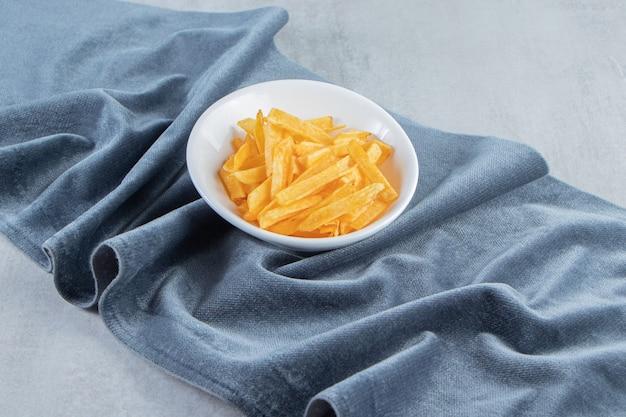 Weiße schüssel mit knusprigen kartoffelsticks auf blauem tuch.