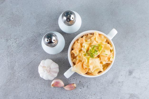 Weiße schüssel mit köstlichen makkaroni mit knoblauch und salz auf steinoberfläche.