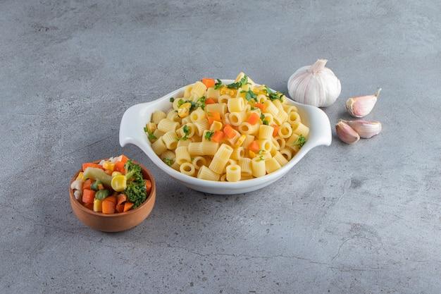 Weiße schüssel mit köstlichen nudeln mit frischem salat auf steinoberfläche.