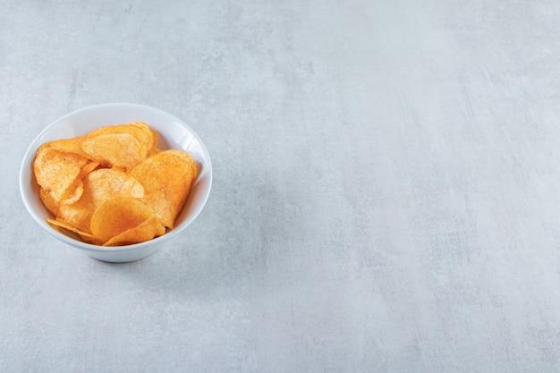 Weiße schüssel mit leckeren kartoffelchips auf stein.