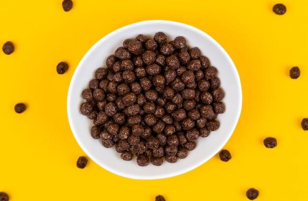 Weiße schüssel mit müslikugeln aus schokoladenmais und milch auf gelb