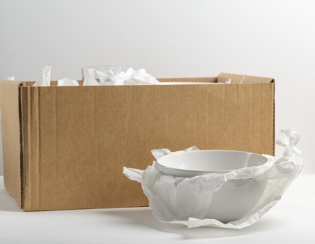 Weiße schüssel mit pappschachtel im paket