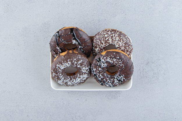 Weiße schüssel mit vier schokoladenkrapfen auf steinhintergrund. foto in hoher qualität